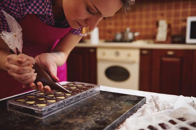 Banketbakker chocolatier knijpen vulling van romige vloeistof bereiden luxe handgemaakte chocoladepralines thuis keuken