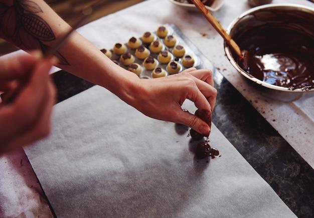 Banketbakker die cacaopoeder bestrooit op een handgemaakte truffel gedoopt in een gesmolten chocolademassa. het vervaardigen van handgemaakte chocoladetruffels