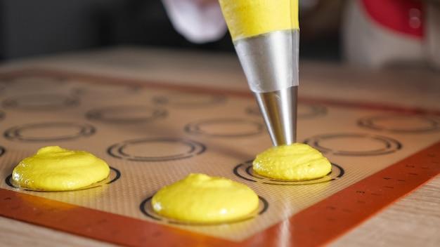 Banketbakker giet deeg uit spuitzak op stencil siliconen mat op tafel. koken bitterkoekjes, close-up. selectieve focus