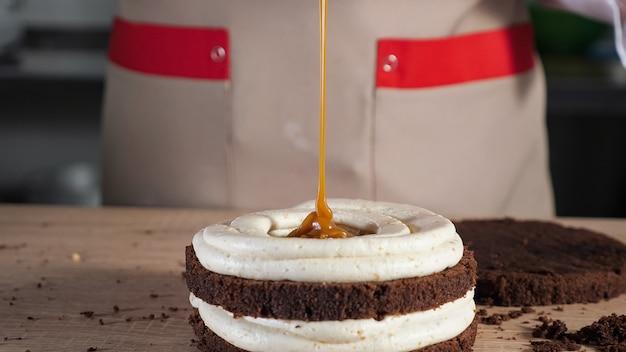 Banketbakker giet karamel op chocoladebiscuit met room. bakken en industriële voedselproductie. close-up bekijken.