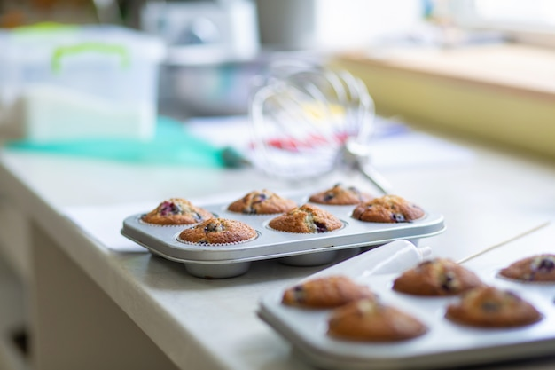 Banketbakker haalde versgebakken muffins uit de oven in een ovenschaal op tafel