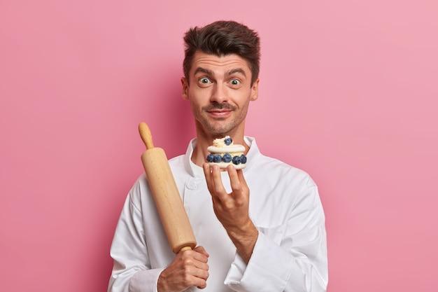 Banketbakker houdt lekkere slagroomtaart vast, vertelt het recept van heerlijke zoetwaren, werkt in het café als kok, gekleed in wit uniform