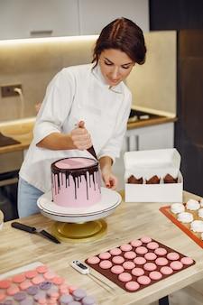 Banketbakker in een uniform siert de taart