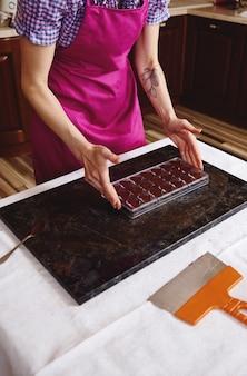 Banketbakker in roze schort houdt chocoladevormen vol met vloeibare verwarmde chocolademassa en zet deze op een marmeren oppervlak. luxe chocolaatjes maken om wereldchocoladedag te vieren