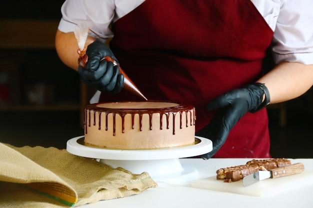 Banketbakker knijpt vloeibare chocolade uit een spuitzak op een crème koektaart