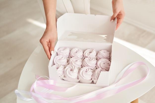 Banketbakker meisje met roze marshmallows in een witte geschenkdoos