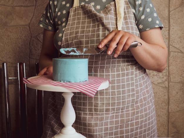 Banketbakker meisje smeert room met een spatel op een vers gebakken verjaardagstaart