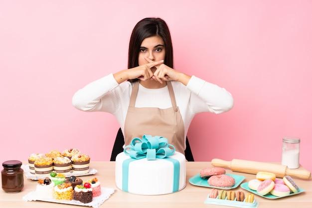 Banketbakker met een grote taart in een tafel over roze muur met een teken van stilte gebaar