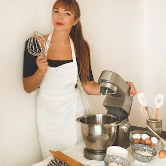 Banketbakker roodharige meisje houdt elektrische zwaaien van de keukenmachine