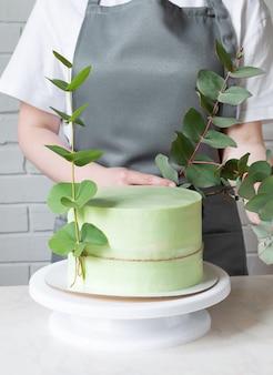 Banketbakker versiert groene cake met eucalyptus.
