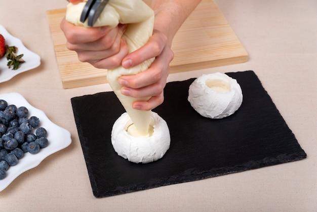 Banketbakker vult de taarten met room. de handen van de chef-kok. proces, bovenaanzicht