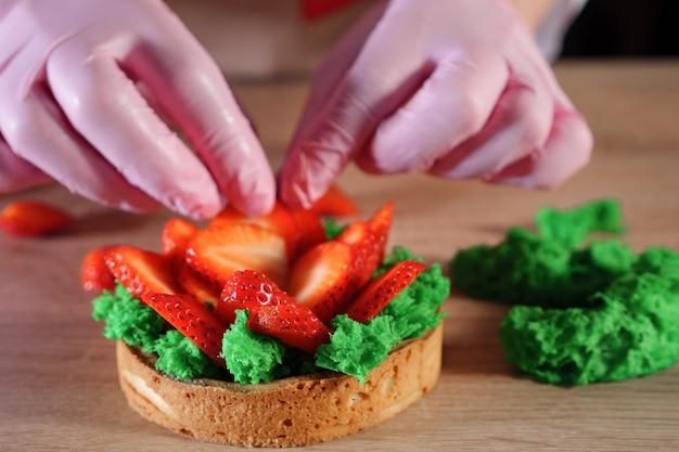 Banketbakker zet aardbeienplakken met room op koekje en maakt een minicake. handen close-up. bakken en industriële voedselproductie