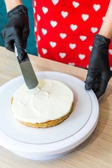Banketbakker zet room op een biscuitgebak. taart maken proces