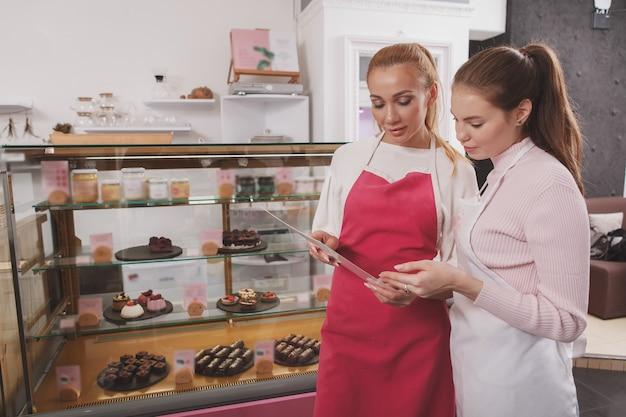Banketbakkers bespreken menu bij rauw veganistisch zoetwaren café en winkel