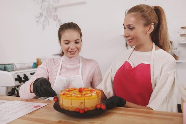 Banketbakkers die heerlijke rauwe veganistische cake versieren, werken in hun café