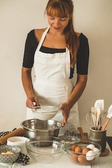Banketbakkersmeisje dat een cake voorbereidt