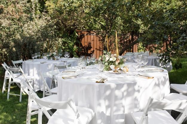 Bankettafel voor gasten buiten met uitzicht op de groene natuur.