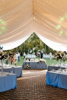 Banketzaal in een tent met blauwe tafelkleden en versieringen