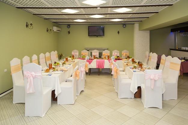 Banketzaal van het restaurant, gedekte feestelijke tafels.