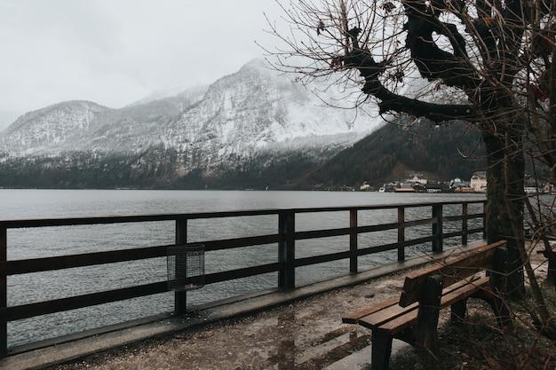 Bankje in de buurt van het meer op een koude dag en besneeuwde bergen