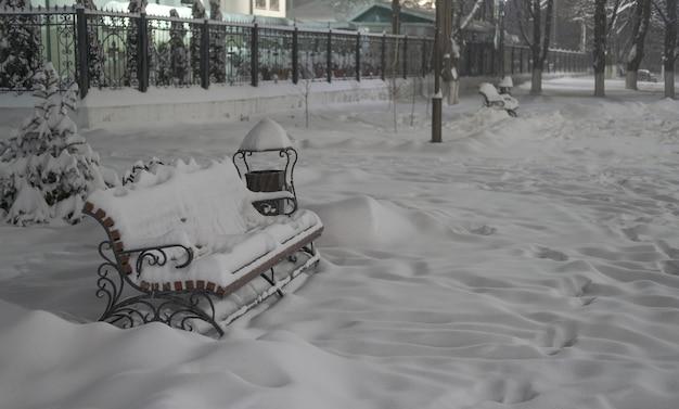 Bankje in een winter park close-up met een grote sneeuwbedekking
