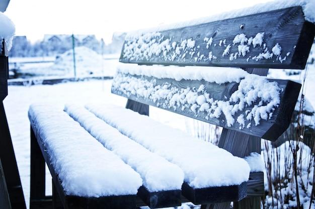 Bankje in het park bedekt met sneeuw