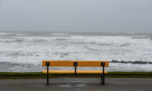 Bankje op het strand, omringd door de zee onder een bewolkte hemel tijdens de storm