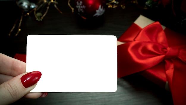 Bankkaart in handen van vrouwen tegen de achtergrond van een geschenk
