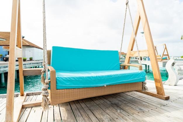 Bankschommel met tropische resort maldiven en zee achtergrond Premium Foto