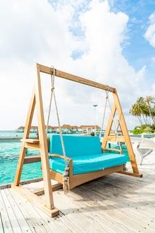 Bankschommel met tropische resort maldiven en zee