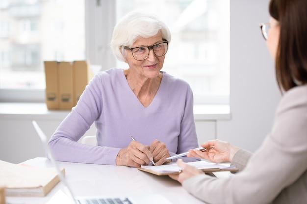 Bankspecialist die hogere dame in glazen vraagt om document voor uitgifte van sociale kaart te ondertekenen