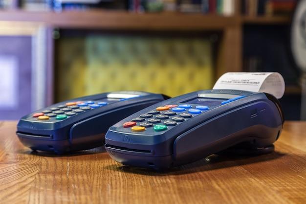 Bankterminal met een gedrukte cheque en gekleurde knopen die zich op een houten lijst bevinden. het concept van het betalen van rekeningen in restaurant en winkel, winkelen met een creditcard