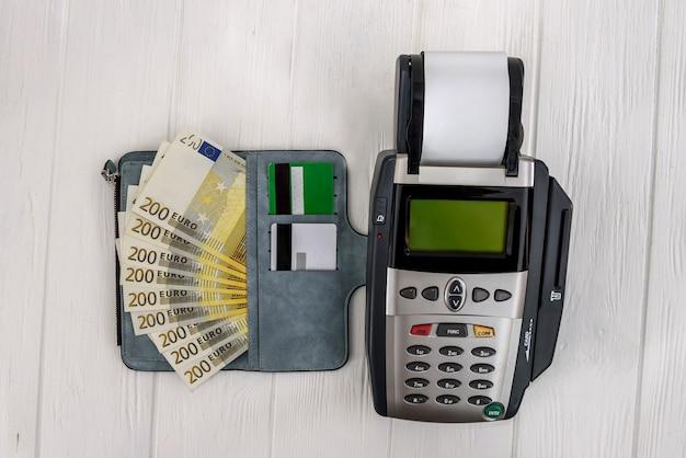 Bankterminal met euro in portemonnee en creditcard