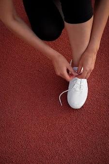 Banner damesbenen. de hand van een vrouw bindt de veters van haar sneakers in het stadion. voorbereiden om te rennen. ruimte voor tekst.