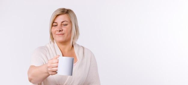 Banner. de blanke vrouw steekt een kopje thee naar de camera. witte achtergrond en lege advertentieruimte. hoge kwaliteit foto
