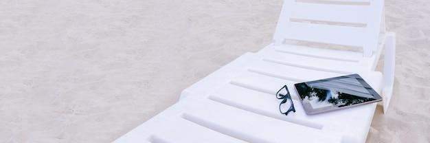 Banner, de mock-up van de tablet ligt op een ligstoel. tegen de achtergrond van strandzand. vakantieconcept.