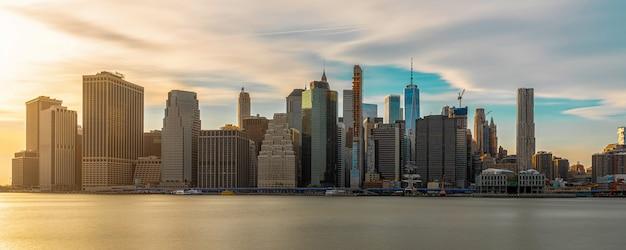 Banner en panorama van new york cityscape met brooklyn bridge over de rivier van het oosten op de avond de tijd