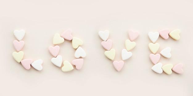 Banner inscriptie liefde met geel roze en witte snoep hartjes op een beige achtergrond.