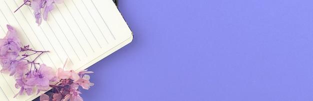 Banner met dagboek en bloem, gezellige notebooksjabloon op paarse achtergrond met kopieerruimte, plat lag en foto van bovenaanzicht