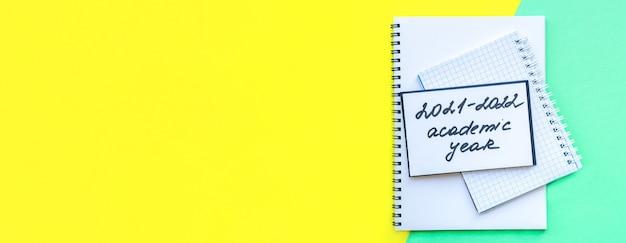 Banner met inscriptie academisch jaar stapel notitieboekjes op spiraaloverlappen helder kleurrijk geel