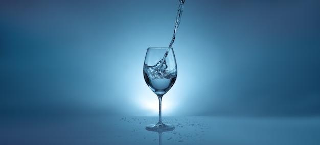 Banner met stromend water in een transparant glas voor wijn. lichtblauwe achtergrond met waterspatten en kopieerruimte