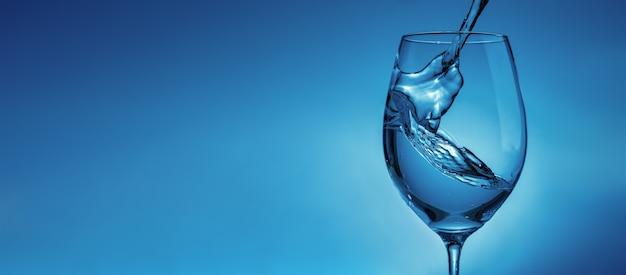Banner met stromend water in een transparant glas voor wijnclose-up. lichtblauwe achtergrond met waterspatten en kopieerruimte