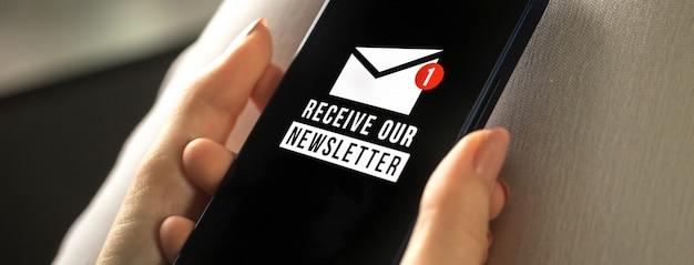Banner, mobiele telefoon met nieuwsbrief aanmeldingspagina close-up in handen van de vrouw. e-mailmarketing of nieuwsbriefconcept, e-mailconceptfoto verzenden