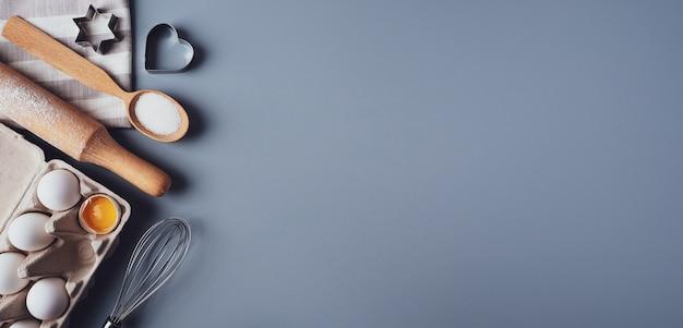 Banner, plat lag samenstelling, ingrediënten voor het bakken van koekjes op een grijze achtergrond, kopie ruimte.