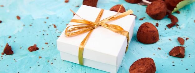 Banner van chocoladesuikergoed truffels vallen uit gouden luxe doos