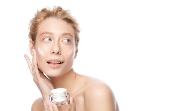 Banner van jonge mooie vrouw met heldere huid die cosmetische pot vasthoudt en gezichtscrème aanbrengt