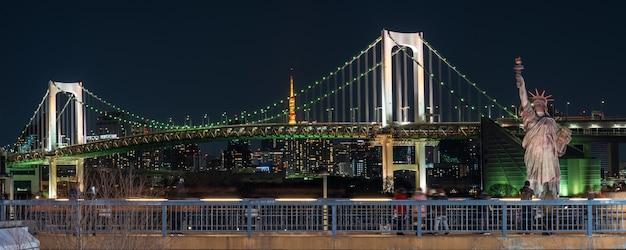 Banner van standbeeld van vrijheid en regenboogbrug bij nacht, gelegen in odaiba tokyo, japan