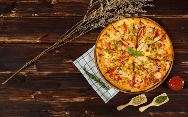 Banner van zelfgemaakte zeevruchtenpizza met garnalen, krabsticks, paprika-topping op houten dienblad, tafel, versierd met tomatensaus, ketchup, oregano-ingrediënten met servet in keuken en kopieerruimte.