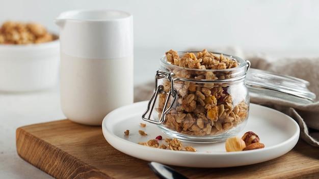 Banner zelfgemaakte muesli met noten in een glazen pot op een houten bord. gezond ontbijtconcept, vegetarisch ontbijt.