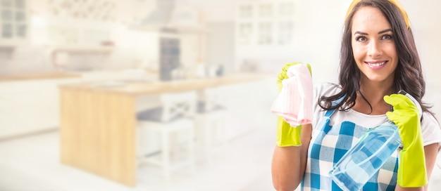 Bannerweergave van een glimlachende mooie vrouw in schort met wasmiddel en schoonmaakdoek in haar handen in rubberen handschoenen in het rechter derde deel van de foto met keuken op de achtergrond.